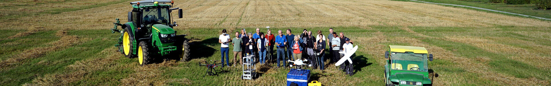 The picture of staff shows the team on a filed with different farming equipment